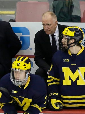 Head coach Red Berenson watches from the bench with Max Shuart (25) and Travis Lynch, right, during the third period of an NCAA college hockey game in the Big Ten Conference tournament Friday, March 20, 2015, in Detroit. Michigan defeated Michigan State 4-1 and will play Minnesota in the championship game Saturday.