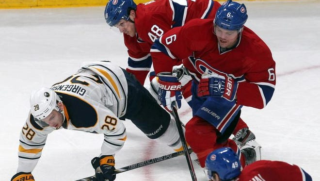 Zemgus Girgensons, who scored for Buffalo, is knocked to the ice by Montreal players in a 3-2 Canadiens' win Saturday.
