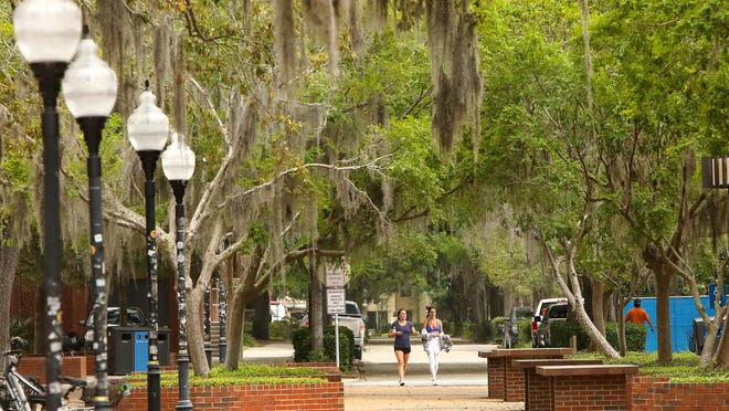 Friends stroll through the University of Florida campus in April after it was shut down by COVID-19. Despite a projected downturn, UF saw a slight increase in applicants for the fall 2021 semester.