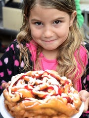 Brianna Ford, 7, of Yellville is all smiles as she prepares to dig into a funnel cake at