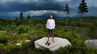 In this Aug. 4, 2015, photo, Lucas St. Clair, the son of Burt's Bees founder Roxanne Quimby, poses on land proposed for a national park in Penobscot County, Maine.  President Barack Obama on Aug. 24, 2016, declared a new national monument in Maine on 87,000 acres donated by Quimby, fulfilling the conservationist's goal of gifting the land during the 100th anniversary of the National Park Service.