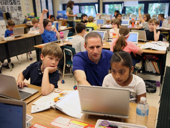 Mike Gray, a third grade teacher at the Cottle School in Tuckahoe, helps students with their assignments on a Chromebook, June 4, 2014.
