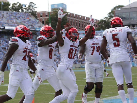 Dez Fitzpatrick (center) and Seth Dawkins (far right) celebrate after Fitzpatrick's second touchdown in Louisville's 2017 win at UNC.
