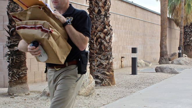 An investigator carries packages as he leaves the Palm Springs City Hall after a raid by the Inland Empire Public Corruption Task Force, Sept. 1, 2015.