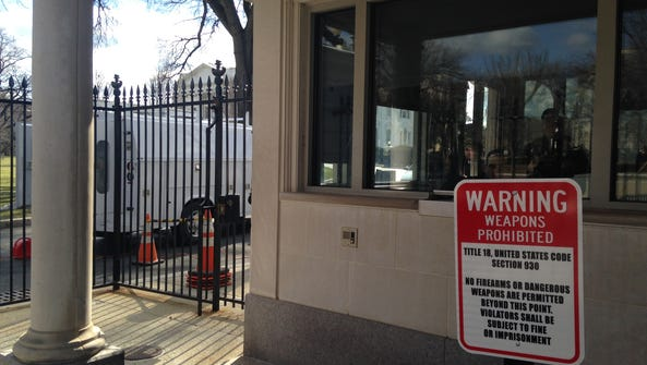 """The """"no firearms"""" sign with the White House in the"""