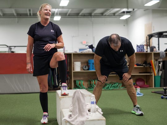 Cathy Kansman, left, has a laugh as her husband Kevin Kansman, right, takes a breather during their workout.