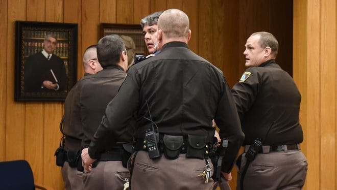 Randall Margraves, surrounded by law enforcement officers, was detained Friday, Feb. 2, 2018, after trying to attack Larry Nassar in Eaton County (Mich.) Circuit Court. The incident occurred during the second day of victim-impact statements after two of his three daughters gave statements against Nassar. Margraves was later released.