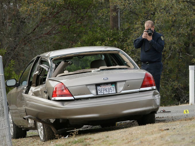 A California Highway patrol officer photographs a vehicle