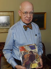 "David Barnhart, a lexicographer, holds a copy of his own book, ""Barnhart's Never-finished Political Dictionary of the 21st Century."""