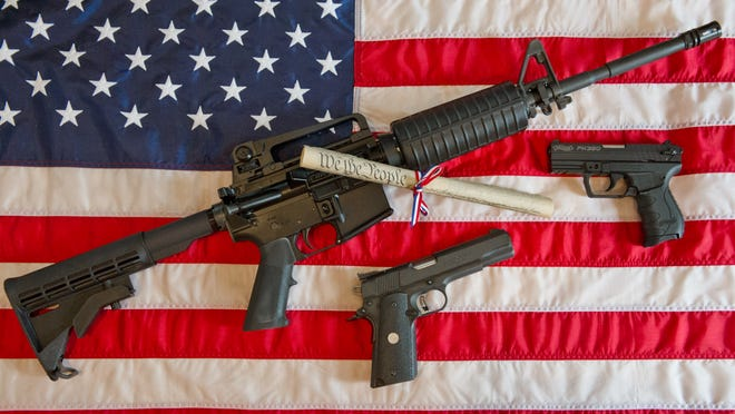 This February 4, 2013 photo illustration in Manassas, Virginia, shows a Colt AR-15 semi-automatic rifle a Colt .45 semi-auto handgun and a Walther PK380 semi-auto handgun and a copy of the U.S. Constitution on top of the American flag.