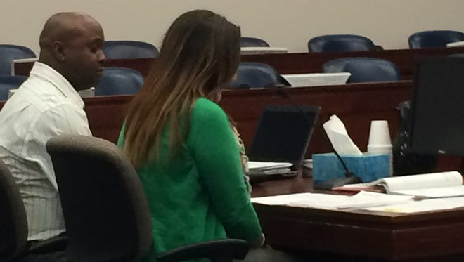 Dominique Nolff's father, Tommy Bouie, looks on as Nolff's mother, Melissa Hurt, speaks.