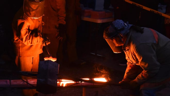 Metal artists pour white-hot, molten iron into individually designed molds that will form art tiles at last year's Community Iron Pour at the Peninsula School of Art.