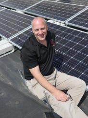 Terry Dvorak poses with the solar panels his Norwalk-based