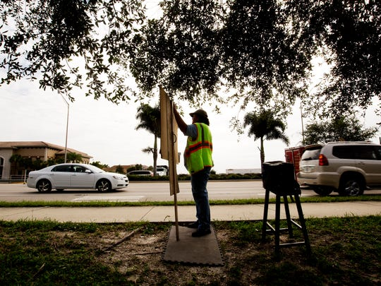 Karen Bickford holds a sign directing passersby to a consignment furniture shop along Airport Pulling Road in Naples on Wednesday.