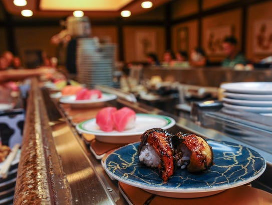 Prepared sushi travel along on a conveyor belt at the