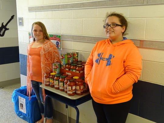Fifth-grader Myla Villareal,(right), helped organize a fundraiser for a local man with ALS. She and fellow fifth-grader Kylee Gamble, (left), show off some of the spaghetti sauce they've collected for the fundraiser dinner.