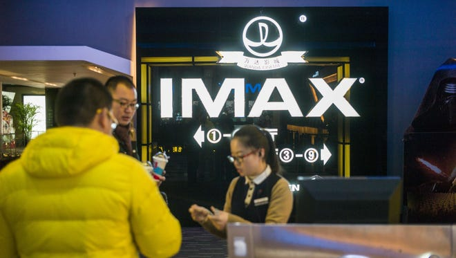 A hostess checks tickets at the Wanda cinema next to the Wanda Group building in Beijing on Jan. 12, 2016.
