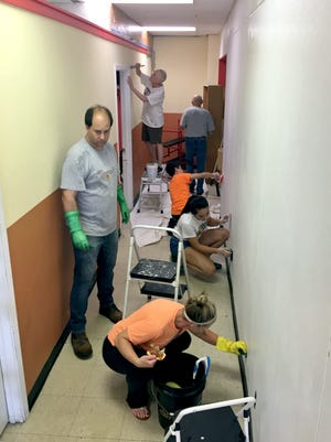 Volunteers from Celebration Lutheran Church help clean up a coffee shop for owner Farhan Abdi in St. Cloud on Sunday, Sept. 10. Abdi hasn't had the time nor resources to get his business running because of work he does with Somali youth.