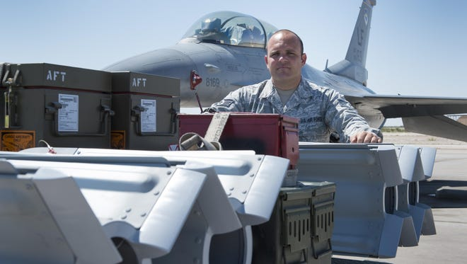 """Staff Sgt. Kenneth, a 49th Maintenance Squadron line delivery crew chief, stands beside a loaded ammunition trailer waiting to arm an F-16 Fighting Falcon on Holloman. """"We are the ones who give the munitions to the people who go and fight,"""" said Kenneth. """"Without our job, those fighter craft are just an expensive airline."""" (Last names are withheld due to operational requirements)."""