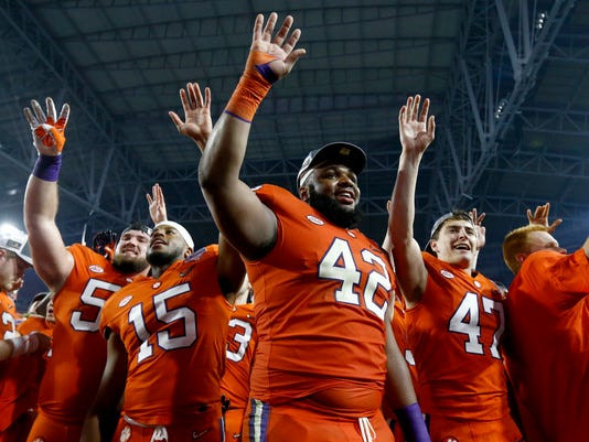 FILE - In this Dec. 31, 2016, file photo, Clemson defensive lineman Christian Wilkins (42), safety Korrin Wiggins (15) and kicker Alex Spence (47) smile and wave after Clemson defeated Ohio State 31-0 in the Fiesta Bowl NCAA college football playoff semifinal, in Glendale, Ariz. it's Wilkins time to be the face of Clemson _ a role the 6-foot-4, 310-pound junior is more than ready to to take on. (AP Photo/Ross D. Franklin, File)
