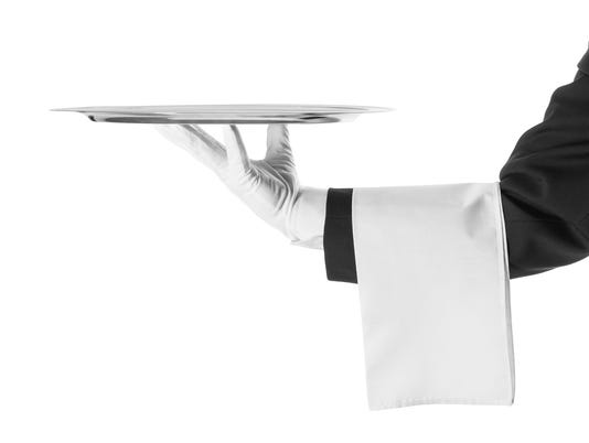 A black and white photo of a waiter holding a platter