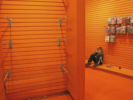 A child sits next to the empty toy displays Wednesday during the last day for the Toys R Us store in New York's Times Square.