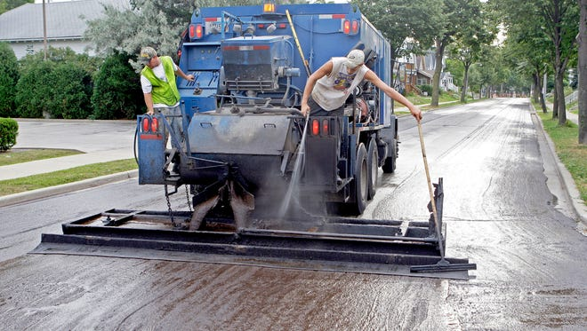 Employees of Struck and Irwin Paving apply a slurry containing an asphalt emulsion and sand as sealant on the 2200 block of E. Bennett Ave. on Milwaukee's south side in 2011.