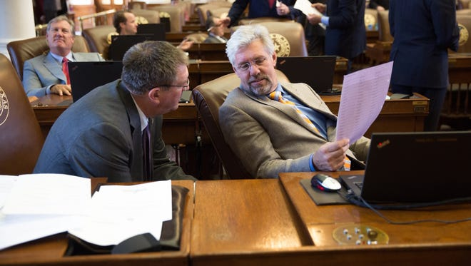 State Reps. Stan Lambert, left, of Abilene, and Lynn Stucky, of Denton, discuss legislation in the House chamber during the 85th session.