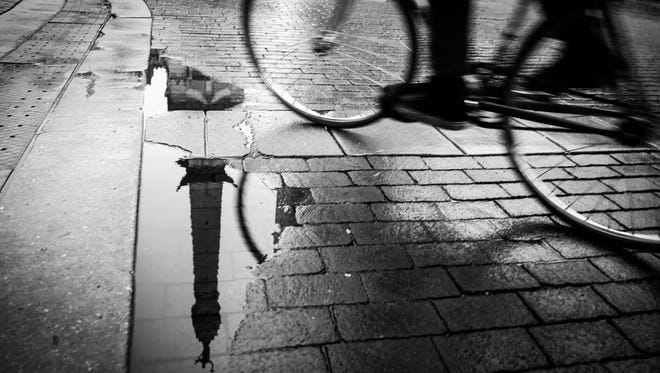 A cyclist rides past the Indiana Soldiers & Sailors Monument, reflected in a puddle on Monument Circle in Indianapolis on Monday, Oct. 23, 2017.