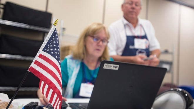A United States flag stands while election volunteers Paula Hunter and Gary Schwartz work at the Larimer County Courthouse on Monday, June 25, 2018.