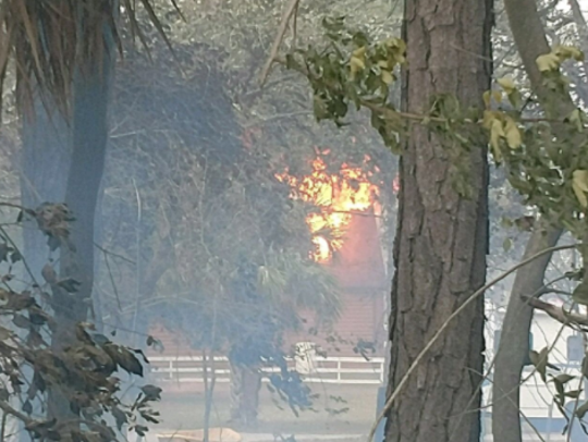Fire threatens this structure in the Lake Washington