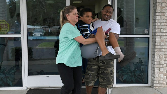 Kristy Mallory helps Phillip Reese carry his son Jeremiah from Beautiful Gate Church after the 10-year-old was injured barricading his Sunday School classroom during the shooting at Burnette Chapel Church of Christ Sunday, Sept. 24, 2017, in Antioch, Tenn.