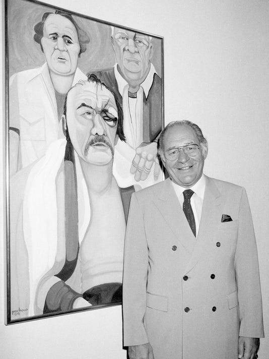 """In this May 10, 1984, file photo, Ferdie Pacheco stands in front of his painting of boxer Chuck Wepner at Manhattan's Spectrum Fine Art Gallery in New York. Fernando """"Ferdie"""" Pacheco, """"The Fight Doctor"""" who served as Muhammad Ali's ringside physician, died Thursday morning, Nov. 16, 2017, at his Miami home after prolonged illness, his daughter, Tina Louise Pacheco, said. He was 89. (AP Photo/Lance Jeffrey)"""