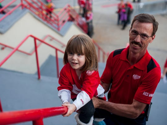 Lacey Hunt, 3, is pushed up the railing outside of Joe Louis Arena by Duane Hunt of Tucson, Arizona, while entering for the Red Wings' game against the Ottawa Senators on Oct. 17, 2016.