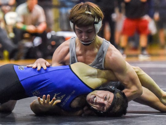 Jensen Beach's Wyatt Kirkham (top) works to pin Sebastian