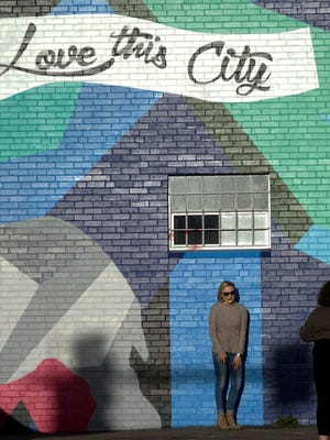 Heather McDonald, 22, poses in front of a mural for a picture being taken by her visiting friend Calista Gorrell, also 22, in downtown Denver. In the city, one of the 20 finalists for Amazon's second headquarters, there's concern winning the bid will exacerbate already significant problems with income inequality.