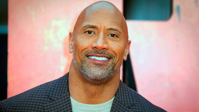 """Dwayne Johnson poses for photographers at the premiere of the """"Rampage,"""" in London. The Pioneer Press reports that Stillwater Area High School Senior Katie Kelzenberg asked if the actor would """"Rock"""" it with her at her May 5 prom in a Twitter video posted last week. The self-proclaimed Johnson fan was dressed like """"The Rock"""" and showed off her collection of Johnson-related merchandise."""