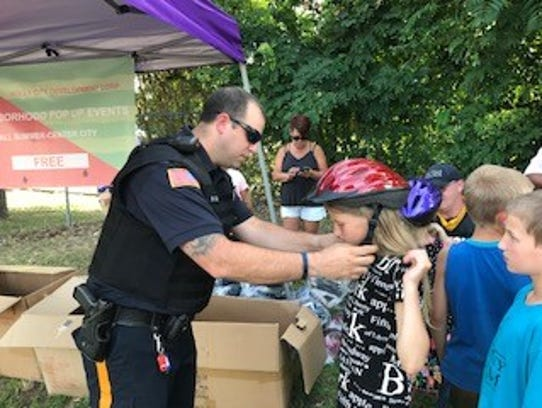 Millville police Officer Sean Guy fits a helmet on