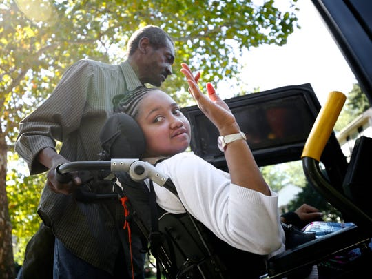 Dreia Davis waves to a crowd as she arrives at her new home on Wednesday, Sept. 23, 2015, in Detroit. Residents of the neighborhood near 7 Mile came out to welcome her.