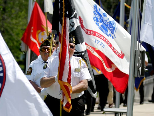 Honor Guard members carry flags as they pass along