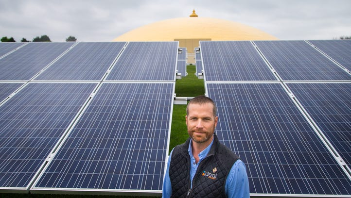 Troy Van Beek stands in front of a solar power array his company Ideal Energy installed at the Maharishi University in Fairfield Monday, May 9, 2016.