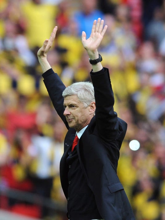 FILE - In this Saturday, May 30, 2015 file photo, Arsenal manager Arsene Wenger salutes the fans after his team won the FA Cup in the English FA Cup Final soccer match between Aston Villa and Arsenal at Wembley stadium, London. Wenger will stay on as Arsenal manager, earning a new two-year contract on Wednesday, May 31, 2017 despite missing out on Champions League qualification. ((AP Photo/Rui Vieira, File)
