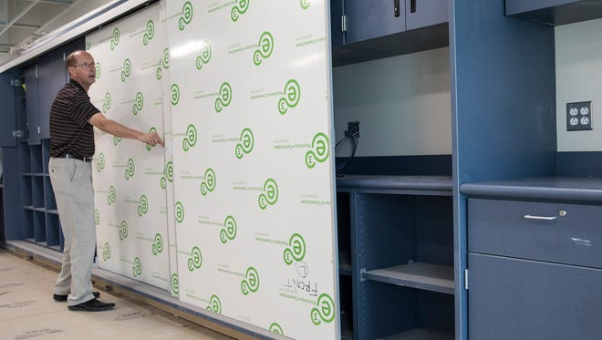 Gone are the days of the blackboard and chalk, Chillicothe School Board President Steve Mullins demonstrates how sliding dry-erase boards will be utilized and how they will cover the student cubbies that will eliminate the need for lockers.