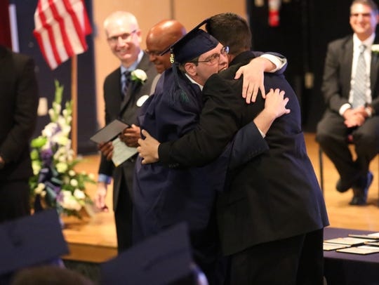 Anderson Center for Autism graduate Brandon Bailey (left) hugs Assistant Principal Jayson Pistritto during the ceremony on Friday. The school honored 18 graduates.