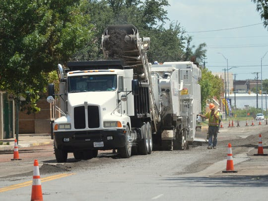 A road crew rips up asphalt on Indiana Avenue in downtown Wichita Falls Tuesday, exposing the old red-brick surface that was used decades ago. City leadership said the asphalt surface is more cost effective than brick, which is why they will overlay the product again.