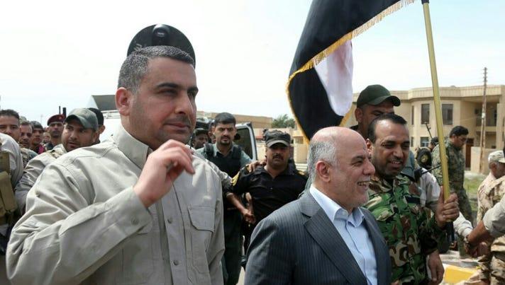 Iraqi Prime Minister Haider al-Abadi, center, walks
