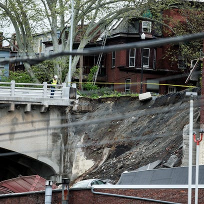 A member of emergency crews looks at a collapsed retaining