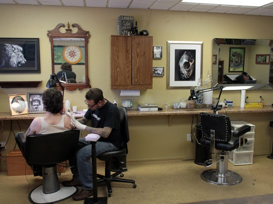 "Ray ""Stingray"" Parrish works on David Zollo's most recent tattoo at Nix Rue Tattoo on Thursday, Sept. 18, 2014."