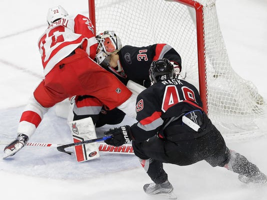 Detroit Red Wings' Andreas Athanasiou (72) collides with Carolina Hurricanes goalie Eddie Lack (31), of Sweden, while scoring the game winning goal during overtime in an NHL hockey game in Raleigh, N.C., Monday, March 27, 2017. Detroit won 4-3. Lack was injured on the play. (AP Photo/Gerry Broome)