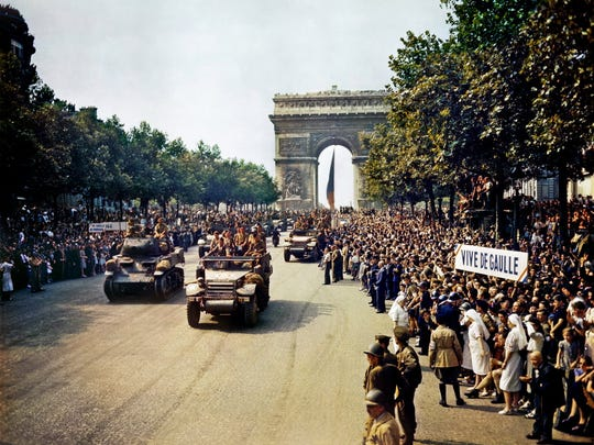 Crowds of French patriots line the Champs-Élysées to view Free French tanks and halftracks of Gen. Philippe Leclerc's 2nd Armored Division pass through the Arc de Triomphe, after Paris was liberated on Aug. 26, 1944.